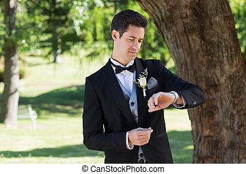 Attractive groom checking time in garden - Young attractive ...