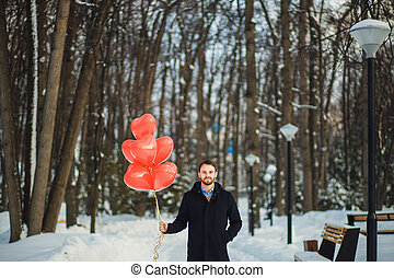 attractive guy in coat with red air balloons in winter park
