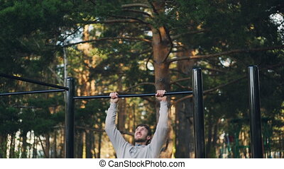 Attractive guy is exercising outdoors using horizontal bar...