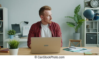 Attractive guy is using laptop typing in office concentrated on business project