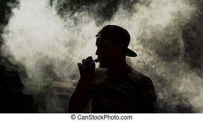 Attractive guy is vaping an ecigarette. Clouds of smoke -...