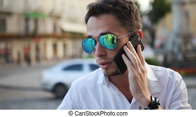 Attractive guy smiling while having a conversation on mobile phone. Close-up picture of handsome man talking on cellphone.