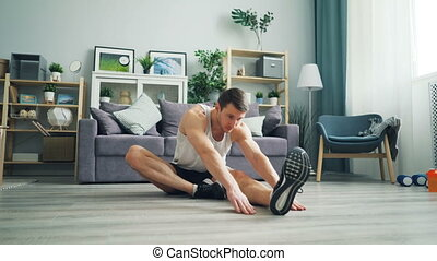 Attractive guy sportsman doing stretching exercises bending...