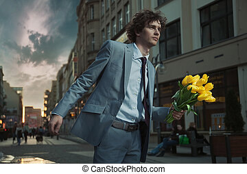 Attractive guy with bunch of tulips