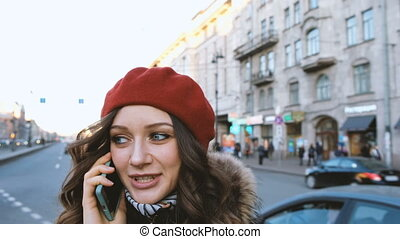 Attractive happy girl talking on the phone on the street in little red riding hood