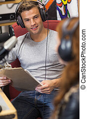 Attractive happy radio host interviewing a guest holding...