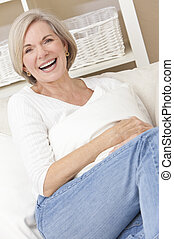 Attractive Happy Senior Woman Laughing at Home - Portrait of...