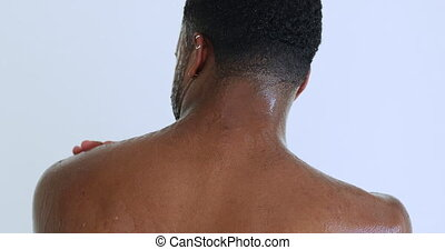 Attractive happy sexy nude young adult african ethnic man taking shower. Smiling afro american muscular hipster guy enjoying washing under warm water in the morning after workout in bathroom at home.