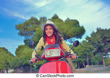 Attractive happy woman on a scooter