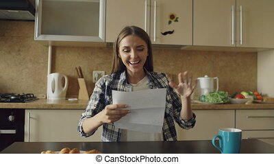 Attractive happy woman recieve good news reading letter in the kitchen while have breakfast at home early morning