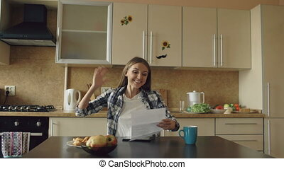 Attractive happy woman recieve good news unfold letter in the kitchen while have breakfast at home