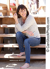 Attractive happy woman sitting on steps outside