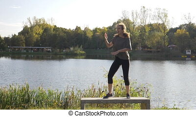 Attractive happy young female student enjoying a day off in the park dancing near to a lake and flipping her hair in slow motion