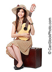 woman sitting on her suitcase while playing guitar