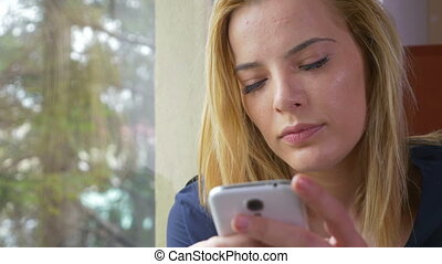 Attractive happy young woman texting a message at the window