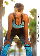Attractive healthy african american woman resting after workout