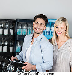 Attractive healthy couple buying bottled water
