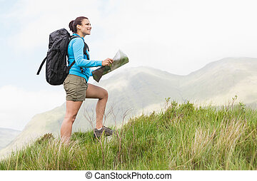 Attractive hiker with backpack hiking uphill holding a map...