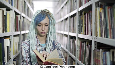 Attractive hipster female student leafing through the book while studying in library with bookshelf background