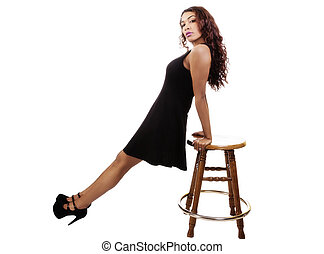 Attractive Hispanic Lady In Black Dress Leaning On Stool