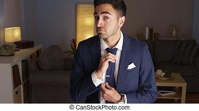 Attractive Hispanic man fixing his tie
