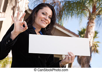 Attractive Hispanic Woman Holding Blank Sign in Front of House