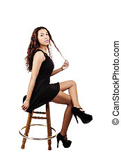 Attractive Hispanic Woman Sitting In Black Dress On Stool