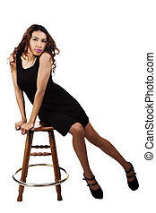 Attractive Hispanic Woman Sitting In Black Dress On Wooden Stool
