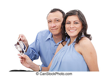 Attractive hispanic young pregnant couple expecting a child holding ultrasound