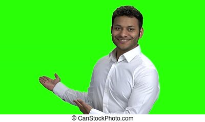 Attractive Indian businessman showing to copy space....