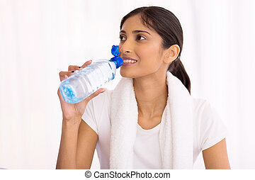 indian woman drinking water after exercise