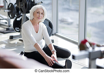 Attractive inspiring senior woman stretching in the gym
