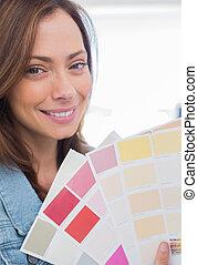 Attractive interior designer holding up colour samples close...