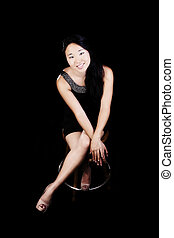 Attractive Japanese American Woman Sitting In Dress On Stool