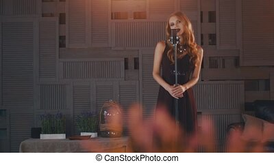 Attractive jazz vocalist in black dress on stage at microphone. Saxophonist