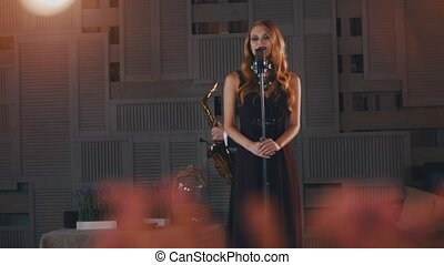 Attractive jazz vocalist in black dress perform on stage with saxophonist. Dance