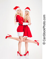 Attractive joyful women in santa claus costumes standing and smiling