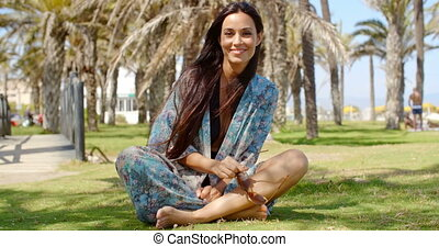 Attractive Lady Sitting on Ground Among Palms