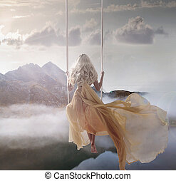 Attractive lady sitting on the swing above the calm lake