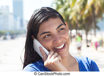 Attractive latin woman with long dark hair at phone in city