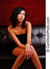 Attractive latino woman sitting on a couch