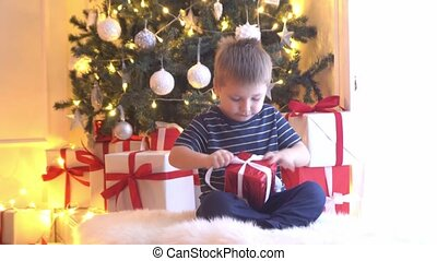 Attractive little boy unwrapping Christmas gifts. Kid opening New Year presents at home.