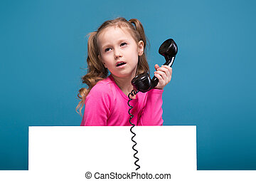 Attractive little cute girl in pink shirt with monkey and blue trousers hold empty poster and talks a phone