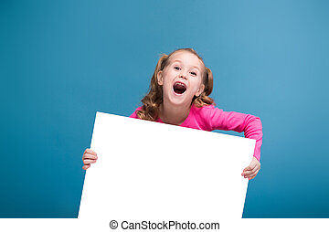 Attractive little cute girl in pink shirt with monkey and blue trousers hold empty poster