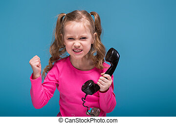 Attractive little cute girl in pink shirt with monkey and blue trousers talks a phone