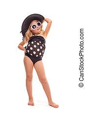 Attractive little girl in in black swimwear, white sunglasses and black hat
