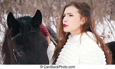 Attractive long haired brunette in a dress and her horse in...