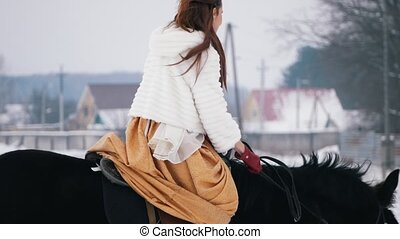 Attractive long haired brunette in a dress on a horse,...