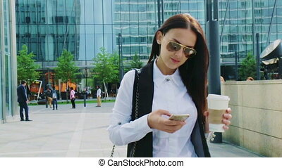 Attractive looking business woman texting while walking