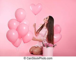 Attractive love brunette woman with balloons and bouquet of rose flowers in hat box isolated on pink studio background.